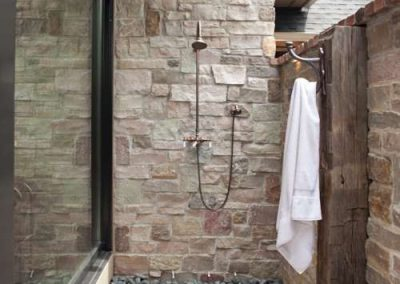 outdoor shower addition in Rustic Medina project by John Kraemer and Sons